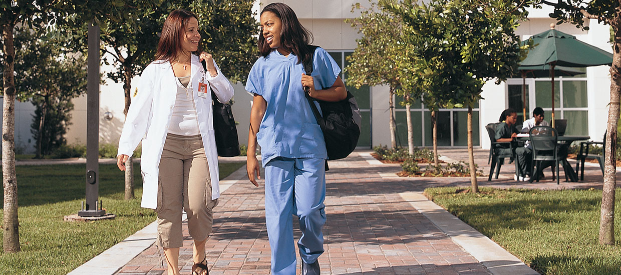 Nursing students walking in front of the School of Nursing and Health Studies