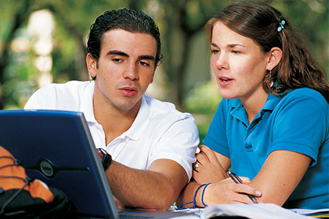 Two students sitting outside and discussing an assignment on their computer